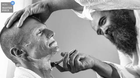 Santorini groom getting shaved before the wedding - South Argean wedding photography
