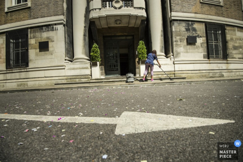 London help cleaning the sidewalk after the wedding - England wedding reportage photo