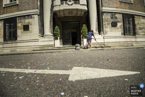 London-Hilfe, die den Bürgersteig nach dem Hochzeit - England-Hochzeitsreportagefoto säubert