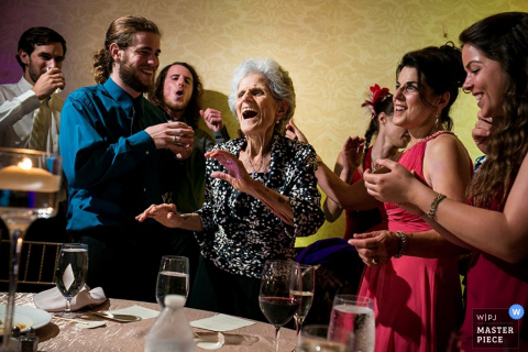 A grandmother and her grandchildren enjoy a moment together at a reception. Picture by a Toronto, Canada wedding photographer.