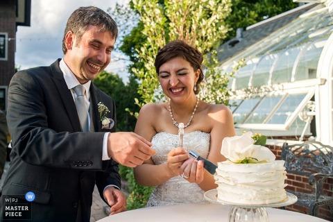 De bruid en de bruidegom van Chicago lachen aangezien zij de cake in openlucht bij de ontvangst - de huwelijksfotografie van Illinois snijden