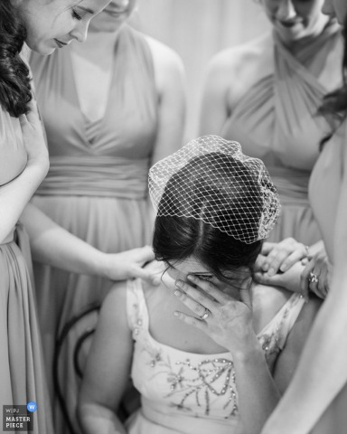 Washington wedding photojournalism image of the bride crying while bridesmaids lay hands on her and pray.