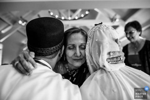 England wedding reportage photo of mom hugging bride and groom.