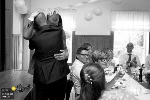 Noord Holland groom hugs best man at the reception - Netherlands wedding photography