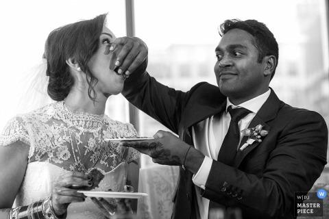 De bruid en de bruidegom die van Chicago elkaar cake voeden bij de ontvangst - het huwelijksfoto van Illinois