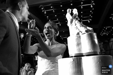 De bruid van Chicago voedt de bruidegom de huwelijkscake bij de ontvangst - het huwelijksfoto van Illinois