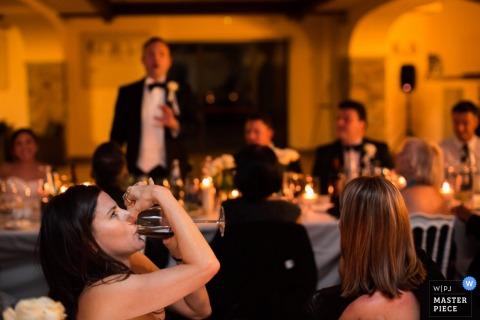 Invitado de Florencia tomando una copa mientras el novio habla en la recepción - Fotografía de boda en Toscana