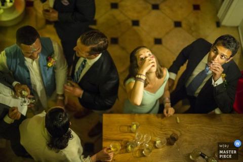 London guests enjoying drinks and shots at the reception bar - England wedding photography