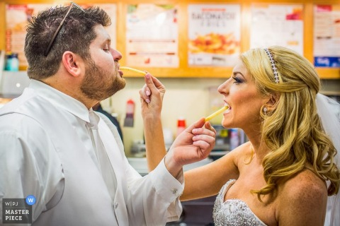 Philadelphia bride and groom feeding each other French fries - Pennsylvania wedding photojournalism