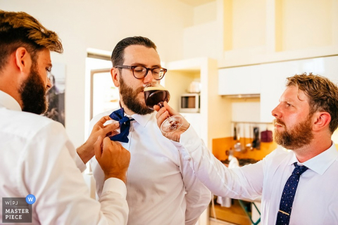 Ljubljana groom getting help with tie and a drink before the wedding - Slovenia wedding photo
