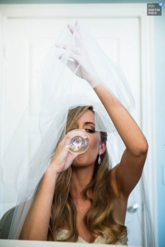 San Francisco bride holds her veil overhead while taking a drink while in her dress - California wedding photo