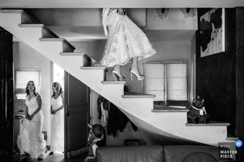 De huwelijksfotograaf van Montpellier veroverde deze zwart-witfoto van een bruid die een open trap afdaalde terwijl haar bruidsmeisjes beneden wachtten