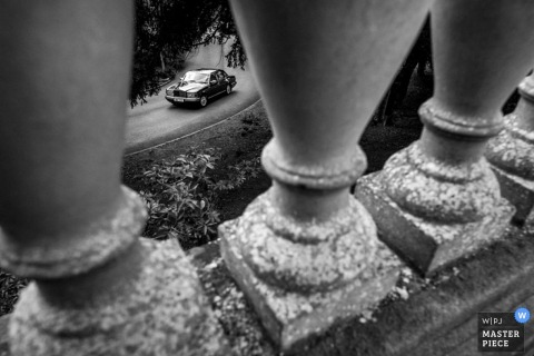 Hertfordshire wedding photographer captured this black and white photo of a vehicle approaching through the columns of a balcony