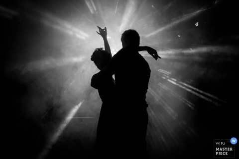 Nantes bride and groom silhouetted while dancing at the reception - Loire Atlantique wedding photojournalism