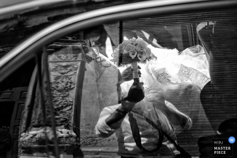 Lecce wedding photographer used a car window to capture this creative shot of the brides bouquet and the groom in the distance