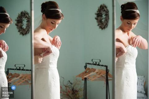 De bruid die van Rome haar kleding in veelvoudige spiegels bevestigt vóór de bruiloft - het huwelijksfotografie van Lazio