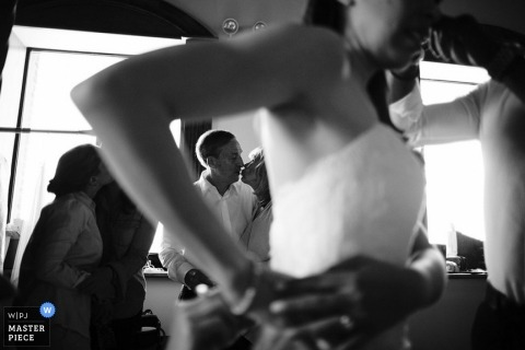 Bronx wedding photographer captured this black and white photo of the bride finishing getting ready as her mother and father kiss in the background
