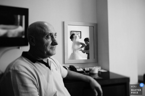 Bronx wedding photographer uses a mirror to capture the bride lacing up her dress while her father sits nearby