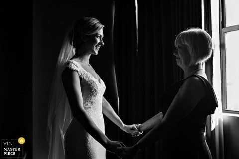 Jacksonville bride holds hands with her mother before the wedding - Florida wedding photojournalism