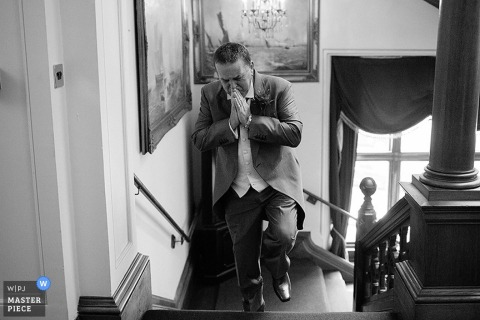 Somerset groom walking up the stairs - England wedding reportage photography