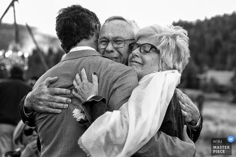 Carson City groom hugs his mom and dad at the wedding - Nevada wedding photojournalism