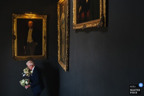 London man holds the flowers for the wedding - England wedding reportage photojournalism