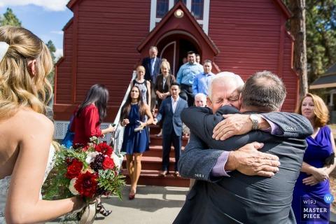 Coeur d'Alene guests hug after the wedding - Idaho wedding photo