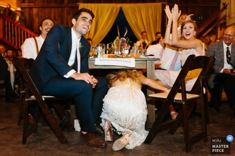 Wedding reception photograph of CA bride climbing under her head table | coverage for San Jose weddings