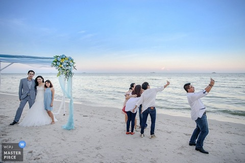 Bangkok guests take selfies of the bride and groom taking pictures on the beach   Thailand wedding photography