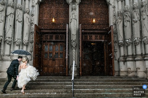 La sposa e lo sposo di Manhattan che camminano sui punti della chiesa con un ombrello | Fotografia di matrimonio di New York