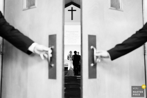 Picture through the doors during the ceremony of the bride and groom at the altar | top Seattle wedding photographer
