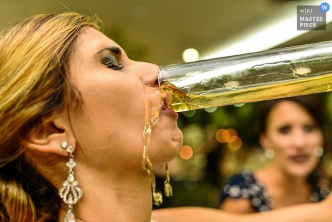 Sao Paulo bride spills some of her drink while drinking it at the reception | Brazil wedding photojournalism