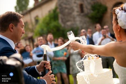 Milan panna młoda i pan młody rozlewają szampana obok tortu ślubnego Fotografia ślubna Lombardii