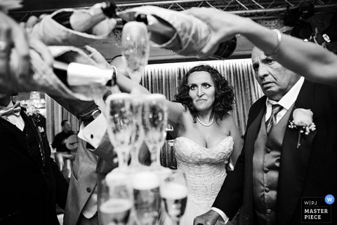 Brooklyn wedding reception photo of bride pouring champaign into tower of glasses
