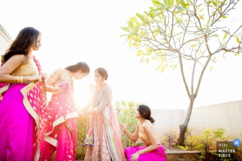 Gujarat bridesmaids helping each other with their dresses before the ceremony | India wedding photo