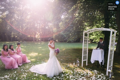 Morbihan bride begins to get emotional as flowers surround her on the ground during the ceremony | Brittany wedding photography