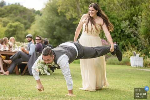 San Francisco-Hochzeitsempfangphotographie eines Paares, das Schubkarre-Rennen mit Blumen tut