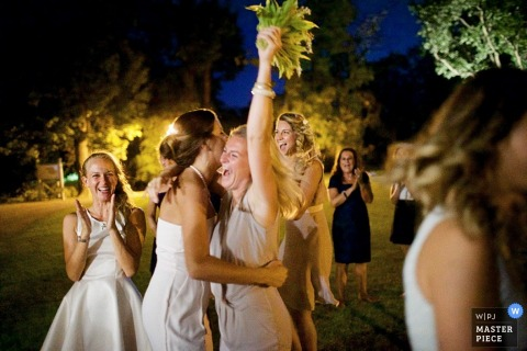 Prague guests clap as the woman holds up the bouquet she just caught | Europe wedding photojournalism