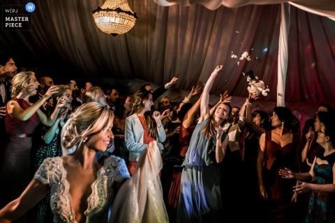 Die Gäste in Toronto versuchen, den Strauß zu fangen, nachdem die Braut ihn geworfen hat Ontario Hochzeitsfoto