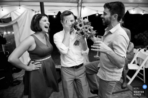 Boston guests laugh together after catching the bouquet at the reception | Massachusetts wedding photojournalism