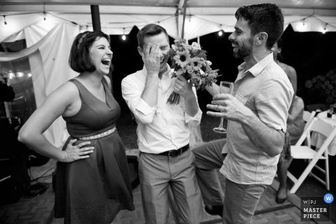 Gli ospiti di Boston ridono insieme dopo aver preso il bouquet alla reception | Fotogiornalismo di matrimoni in Massachusetts