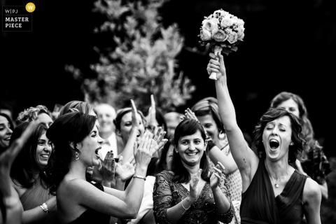 Lecco gasten klappen als een meisje het boeket omhoog houdt Lombardia bruiloft fotojournalistiek