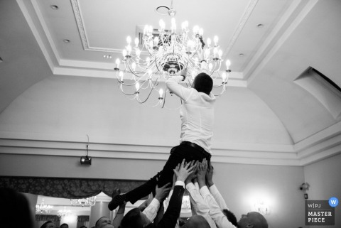 Malopolskie wedding reception photo of guys lifting groom