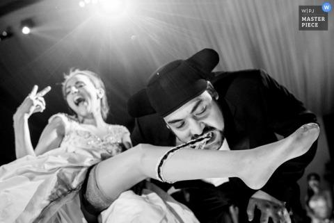 Photographie de réception de mariage du marié enlevant la jarretière de la mariée | couverture pour les mariages de Ljubljana