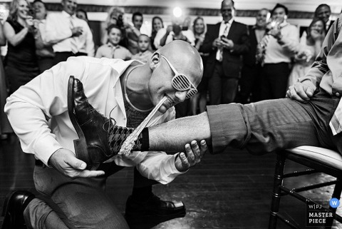 Wedding reception photography of groom and garter on a man | coverage for Brooklyn, NY weddings