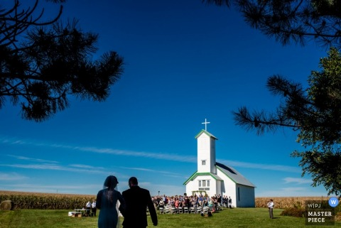 Omaha bride and her father walking towards the outdoor ceremony at the country church| Nebraska wedding photo