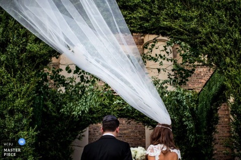 wedding photograph from windy Chicago event | wedding ceremony veil blows for bride