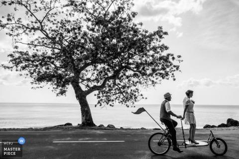 De bruid en bruidegom van Montpellier berijden een fiets naast het water Herault huwelijksfoto