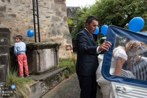 Nouvelle-Aquitaine bride and groom get into car as little boy uses bathroom   France wedding photography