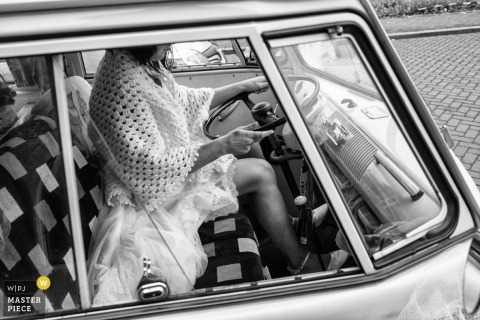 Noord Holland bride driving a car with a blanket around her | Netherlands wedding photojournalism
